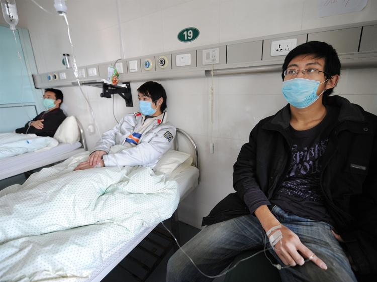 Chinese swine flu patients undergo treatment at a hospital in Hefei in eastern China's Anhui province on Nov 25. The number of infected patients is so high in China that some doctors are telling patients to stay home in quarantine. (STR/AFP/Getty Images)