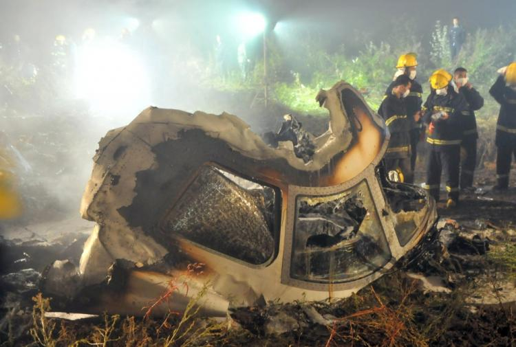 Chinese firefighters search the cockpit of the Henan Airlines ERJ-190 jet wreckage at the crashsite in the northeast city of Yichun in remote Heilongjiang province early on August 25, 2010. A large number of Chinese pilots falsify their flight credentials in order to land better jobs. (STR/AFP/Getty Images)