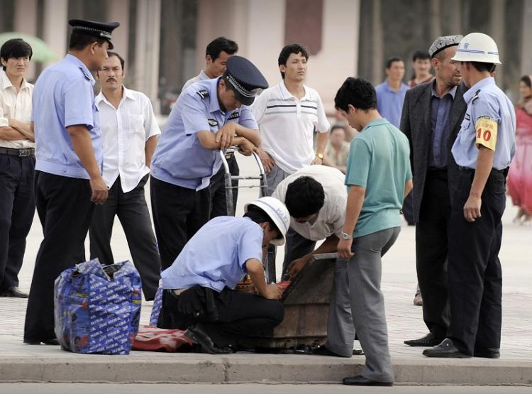Police in Kashgar (a major city along the Silk Road in Northwestern Xinjiang) stop a few ethnic Uighurs to inspect their bags. (AFP/Getty Images)