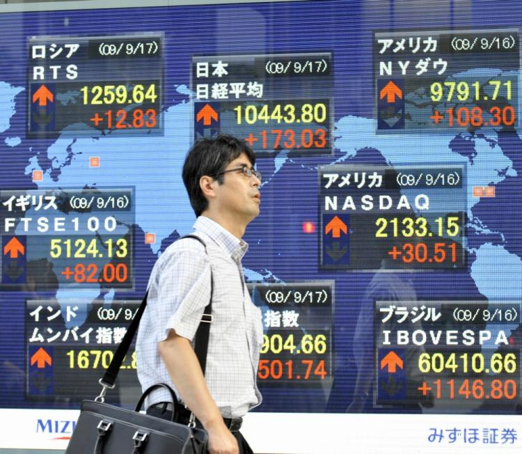A businessman passes before a share prices board in Tokyo. Beijing purchased a net 457 billion yen (US$5.3 billion) of Japanese government debt in June. (Yoshikazu Tsuno/AFP/Getty Images)