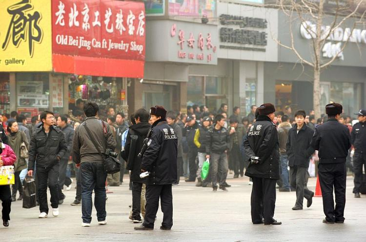 Police keep watch along the Wanfujing shopping street in Beijing after protesters gathered on February 20, 2011. Postings circulating on the Internet called on disgruntled Chinese to gather in public places in 13 major cities to mark the 'Jasmine Revolution' spreading through the Middle East. (Peter Parks/AFP/Getty Images)