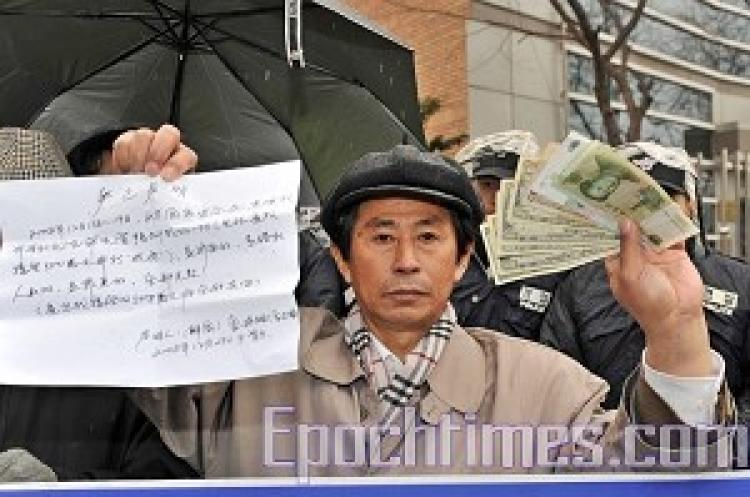 Qihao Jin shows the media the $500 that the CCP authorities gave him to be a secret agent (Zheng Renquan/ The Epoch Times)