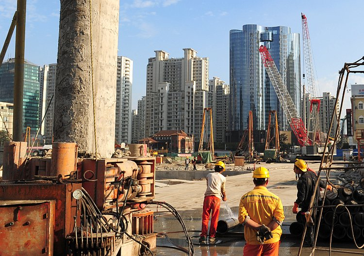 Laborers work at a new property development under construction in Shanghai