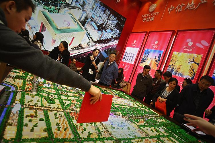Sales people introduce properties to potential buyers at the 2008 Beijing Autumn Real Estate Trade Fair in Beijing, China. (Feng Li/Getty Images)