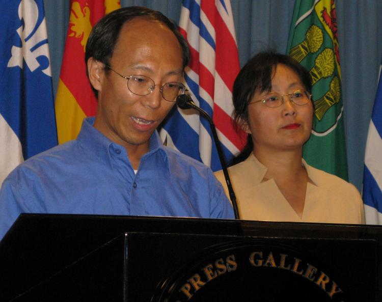 Former Falun Gong prisoner of conscience He Lizhi speaking at a press conference on Parliament Hill in Ottawa on August 1. Mr. He was imprisoned for 3 1/2 years in China. To the right is Lucy Zhou, spokesperson for the Falun Dafa Association of Canada. (Donna He/The Epoch Times)