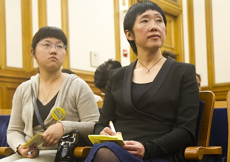 Helena Li (L) and Da Fang sit in the public hearing room at City Hall, waiting to give testimony to the Board of Supervisors. They would explain how the hanging of the red flag of communist China from City Hall startled them, because of their experience of political persecution in China. (Matthew Robertson/The Epoch Times)