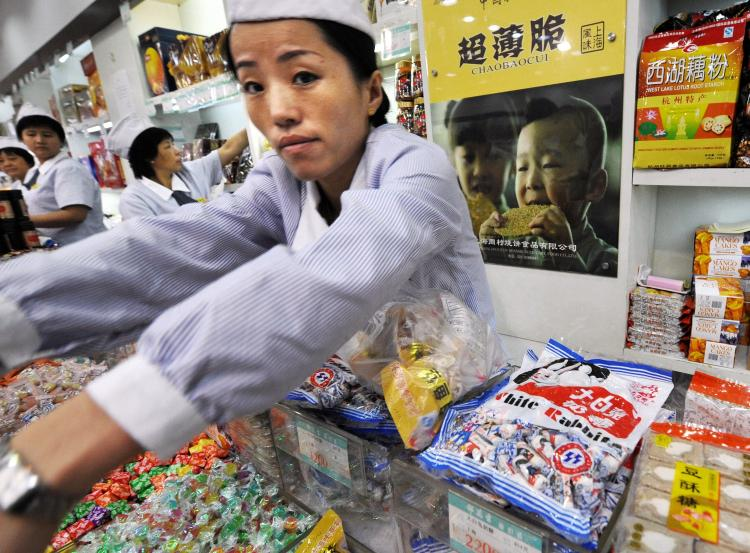 A Chinese shopkeeper serves a customer next to packets of White Rabbit candy on sale at a food store in Shanghai. White Rabbit candy has been found to be contaminated with melamine. (Mark Ralston/AFP/Getty Images)