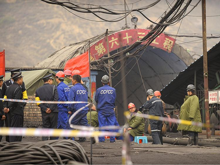 Mine workers and police gather at the entrance to the Wangjialing coal mine where 115 workers were pulled out alive from the flooded mine being built in China's Shanxi province on April 7, 2010. (Peter Parks/AFP/Getty Images)