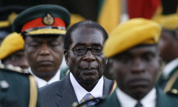 Zimbabwean President Robert Mugabe walks with a guard to be sworn in for a sixth term in office in Harare, on June 29, 2008 after being declared the winner of a one-man election. (Alexander Joe/AFP/Getty Images)