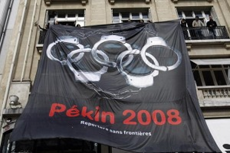 RSF Media rights activists (Reporters without Borders) display a giant banner with the five Olympic rings turned into handcuffs on the Champs Elyses during the Beijing Olympic flame's tour of Paris. (Thomas Coex/AFP/Getty Images)
