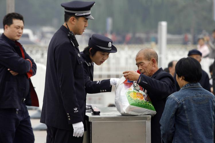 A policewoman checks a man's bag on Tiananmen Square in Beijing ahead of the 17th National Congress of the Communist Party of China in October 2007. Intense security measures are already in place for next month's Beijing Olympics. (Peter Parks/Getty Images)