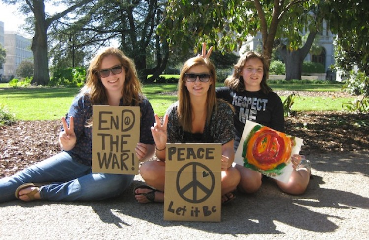 Sarah Rowl, Jenna Cooley, and Miranda Kinard hold up signs for peace and no wars. Cooley said she hopes for a better community. (Kelly Ni/The Epoch Times)