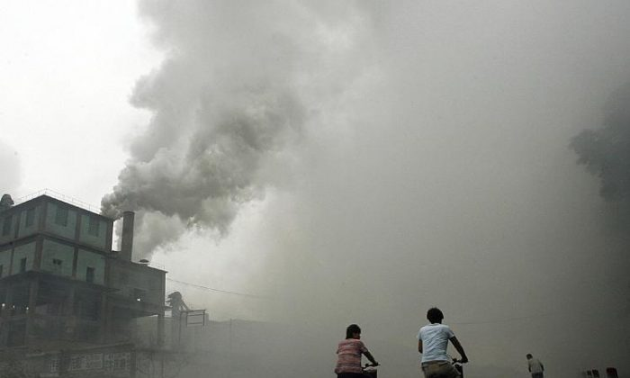 Occupational Hazard: Cyclists pass through thick pollution from a factory in Yutian, Hebei Province, China, in 2006. The surrounding area has a high rate of cancer and death and many villagers are harassed as they try to seek justice. (Peter Parks/AFP/Getty Images)