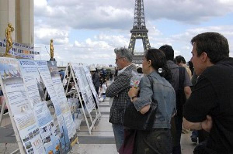Tourists from all over the world reading the signs at the Paris Human Rights Square. (The Epoch Times)