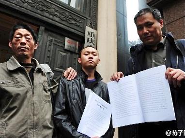 Ren Jianyu, with his father Ren Shiliu (L) and lawyer Pu Zhiqiang (R)
