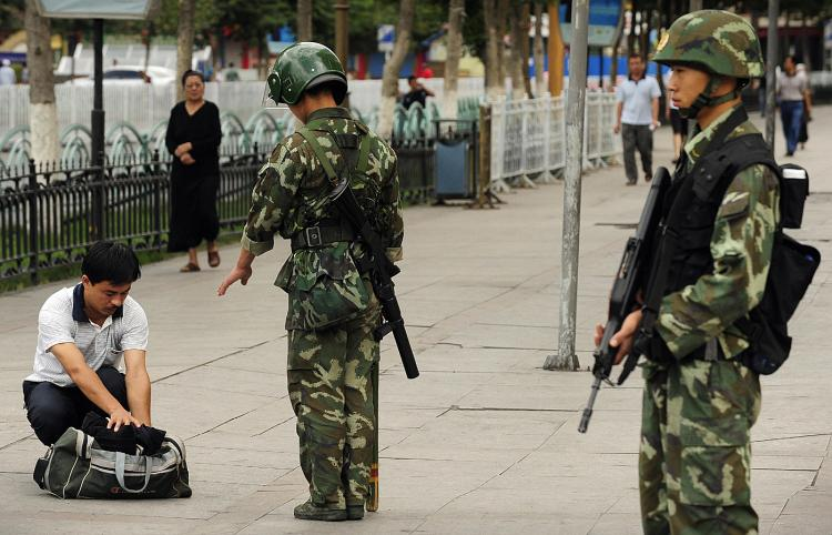Chinese paramilitary policemen search a man's bag on a street in the Uighur district of Urumqi city, in China's Xinjiang region on July 14, 2009. (Peter Parks/AFP/Getty Images)