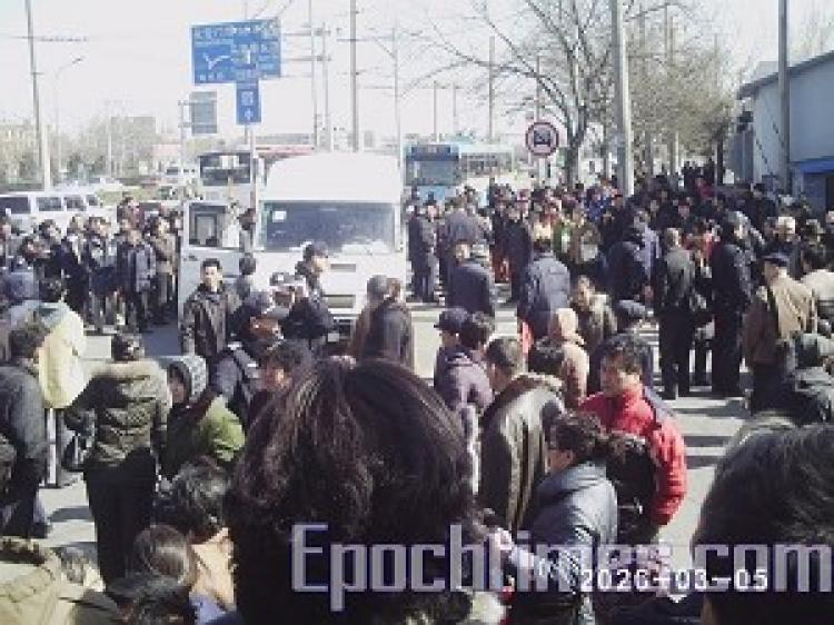 A young girl was brutally beaten at the Beijing Southern Train Station by police who were attempting to stop appellants. Over one thousand angered on-lookers surrounded and beat police, and smashed their car. (The Epoch Times)