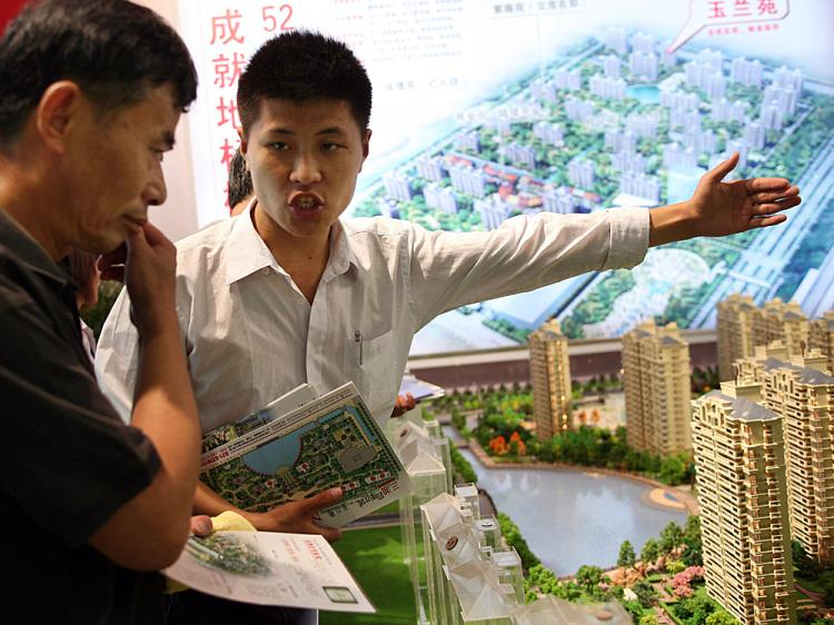 A salesman introduces property to a potential buyer at the Shanghai Real Estate Trade Fair And Exhibition on July 11, 2008 in Shanghai, China. Sales transactions in 10 Chinese cities including Beijing, Shanghai, Guangzhou and Shenzhen decreased 41 percent (China Photos/Getty Images)