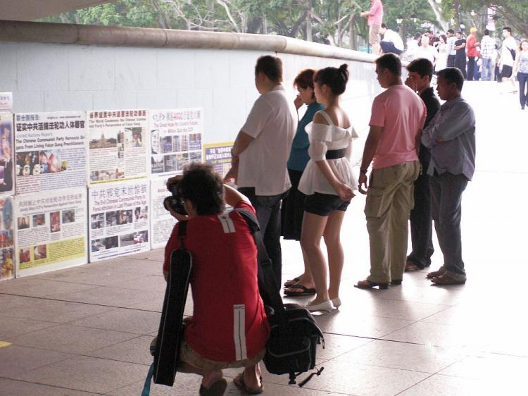 People read posters detailing the persecution of Falun Gong in China. The posters are at the walkway below Esplanade Bridge, in Esplanade Park, Singapore. (Mingguo Sun/The Epoch Times)