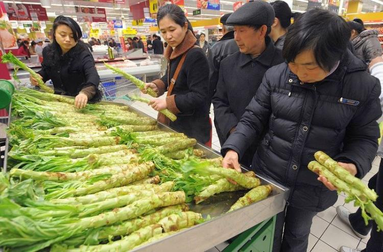 Customers check vegetable prices at a supermarket in Hefei City, Anhui Province, on April 13. (AFP/Getty Images)