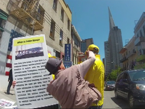A man delivers a blow to the jaw of Falun Gong practitioner Derek Wang.