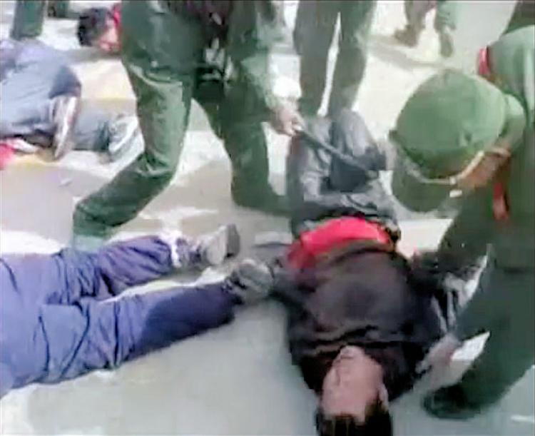 The Tibetan prisoners have their hands tied behind their backs and can only curl in an attempt to resist the beatings. (Tibetan Government-in-Exile Video)