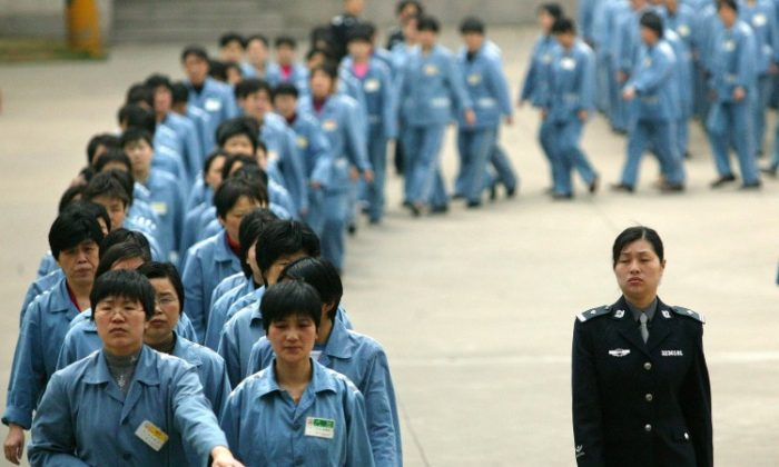 Prisoners walk beside a police escort during a prison open day in Nanjing, 11 April 2005, in eastern China. (STR/AFP/Getty Images)