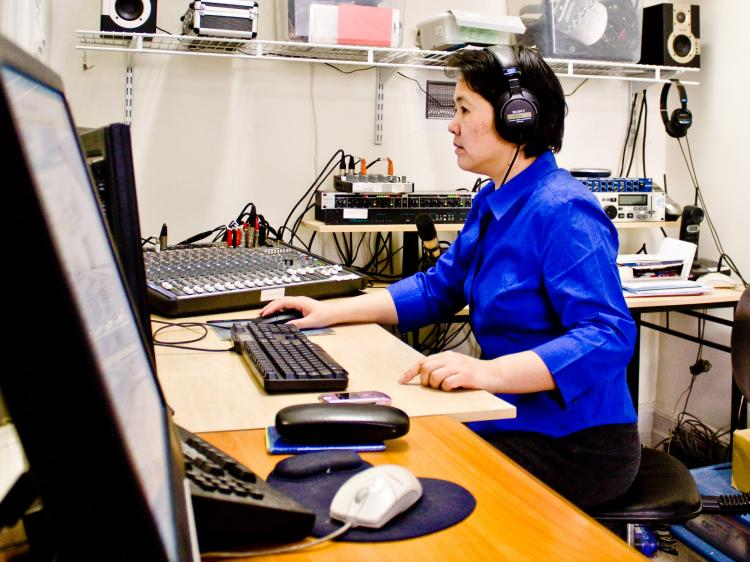 Yue Chen sits at her computer, part of the modest set-up at Sound of Hope's Manhattan office. She has been with the broadcaster, which focuses on human rights in China, since its inception in 2003.  (Matthew Robertson/The Epoch Times)