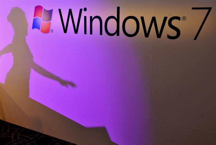 The sihouette of a woman is seen against the logo of the Windows 7 operation system, during a launch party in Taipei on October 23, 2009. (Sam Yeh/AFP/Getty Images)