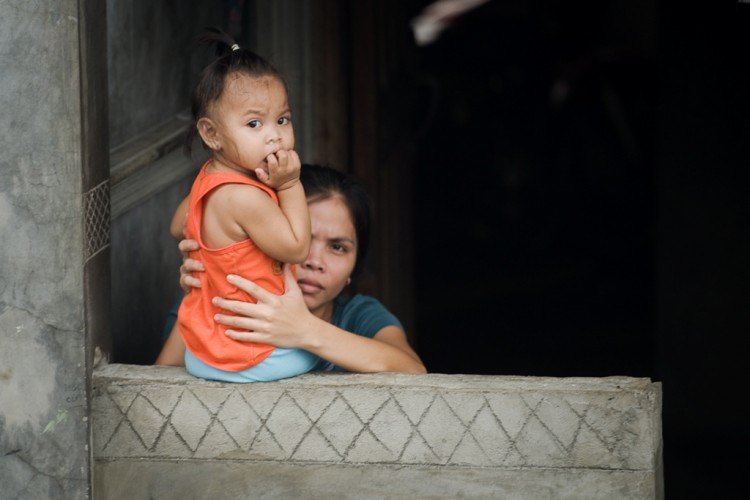 A woman supports a baby on a wall outside their home in Manila on Aug. 10. The Philippines high birth rate is correlated with widespread poverty. (Nicolas Asfouri/AFP/GettyImages)