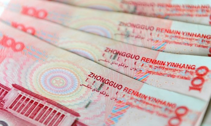 An illustration of Chinese currency 100 yuan notes issued by the People's Bank of China, with an image of parliament building the Great Hall of the People on the rear in Beijing. (Frederic J. Brown/AFP/Getty Images)