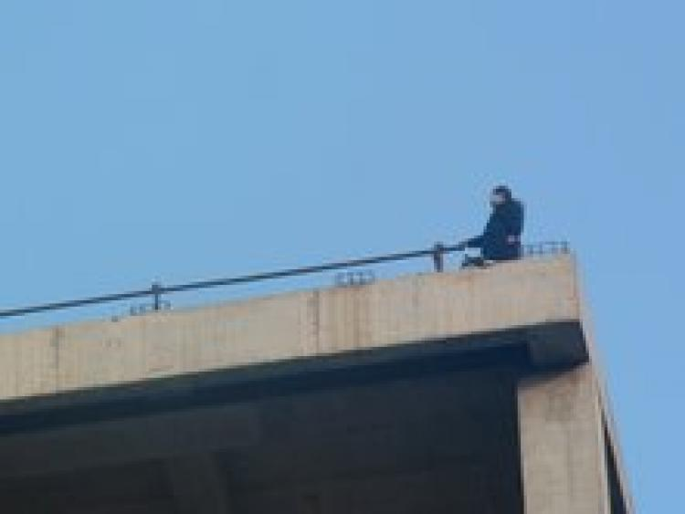 Pregnant petitioner Zhao Chunhong climbed to the top of a tall building in Beijing, hung a banner, scattered leaflets and even sought to jump off the building all in protest of corrupt officials.  (The Epoch Times)