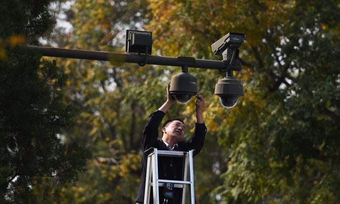 A worker adjusts security cameras on the edge of Tiananmen Square in Beijing on Sept. 30, 2014. (Greg Baker/AFP/Getty Images)