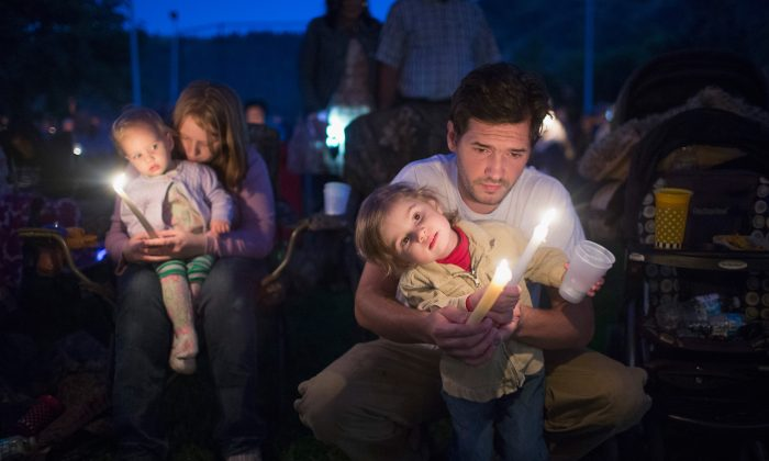 Kyle Workman, his wife Christina, and their daughters Pepper (L) and Samantha attend a prayer service and candlelight vigil at River Bend Park to remember the victims of the mass shooting at Umpqua Community College in nearby Roseburg, in Winston, Oregon, on Oct. 3, 2015. On Thursday 26-year-old Chris Harper Mercer went on a shooting rampage at the college killing nine people and wounding another nine before killing himself. Both Kyle and Christina were students at the school. (Scott Olson/Getty Images)