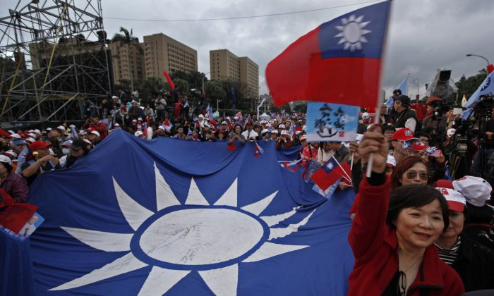 A supporter of Taiwan's President and presidential candidate Ma Ying-jeou waves a national flag during an election campaign rally Sunday, Jan. 8, 2012 in Taipei, Taiwan. Taiwan will hold its presidential election on Jan. 14. (AP Photo/Vincent Yu)