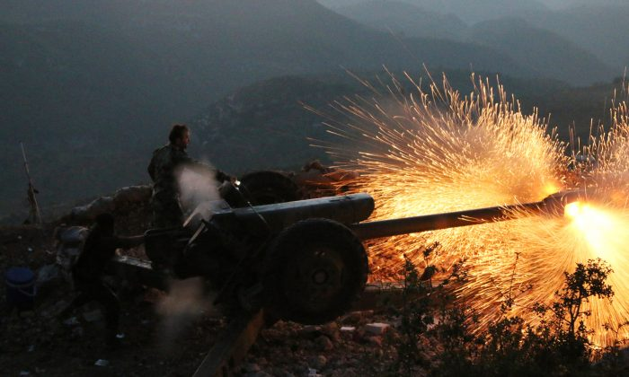 Syrian army personnel fire a cannon in Latakia Province, about 12 miles from the border with Turkey in Syria. Backed by Russian airstrikes, the Syrian army has launched an offensive in central and northwestern regions. (Alexander Kots/Komsomolskaya Pravda via AP)