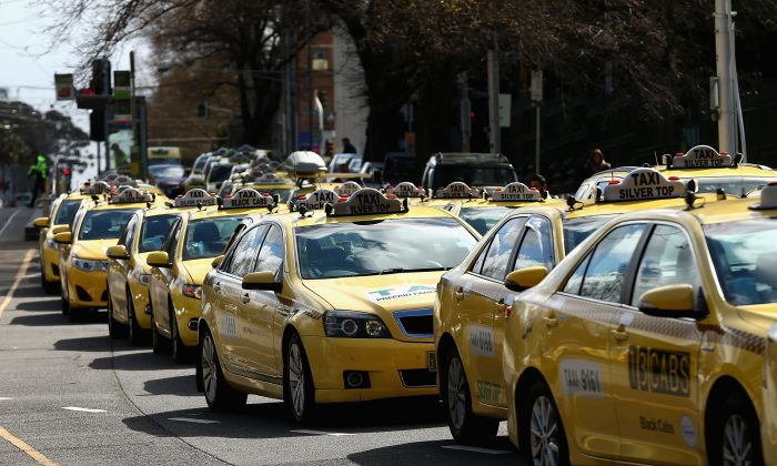Taxi cars are lined up as protesters gather on September 10, 2015 in Melbourne, Australia. Tram drivers are striking for over a pay dispute between drivers and employer Yarra Trams, while taxi drivers are walking off the job in protest of the illegal rideshare service UberX.  (Photo by Robert Prezioso/Getty Images)