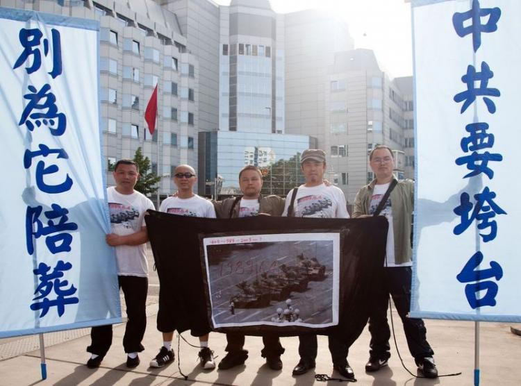 Outside the Chinese embassy in Berlin in 2009 (from left): Zhang Jian, Duan Xinjun, Aobo, Wang Menglong, and Zeng Lunxing. The banner reads, 'The CCP is succumbing; don't get buried along with it.' (Jason Wang/The Epoch Times)
