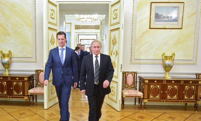 Russian President Vladimir Putin (R) and Syria President Bashar Assad arrive for their meeting in the Kremlin in Moscow, on Tuesday. (Alexei Druzhinin/RIA-Novosti via AP)