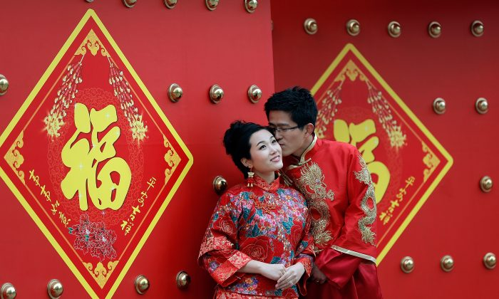 A couple dressed in traditional Chinese costumes have wedding portraits made on Valentine's Day February 14, 2013 in Beijing, China.(Lintao Zhang/Getty Images)