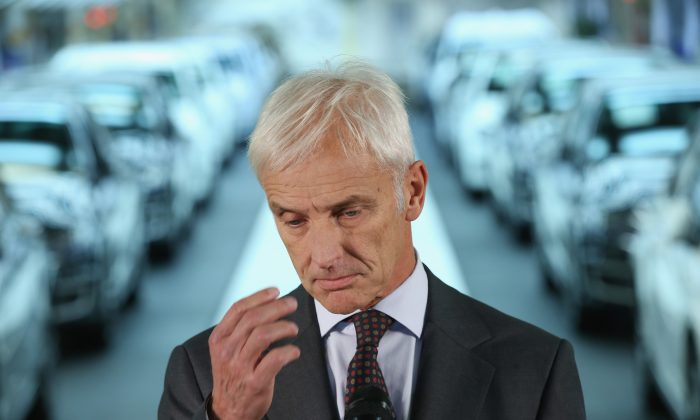 New Volkswagen Group Chairman Matthias Mueller speaks to the media with Volkswagen Work Council head Bernd Osterloh and Lower Saxony Governor Stephan Weil (both not pictured) while standing at the assembly line of the Volkswagen factory in Wolfsburg, Germany, on Oct. 21, 2015. (Photo by Sean Gallup/Getty Images)