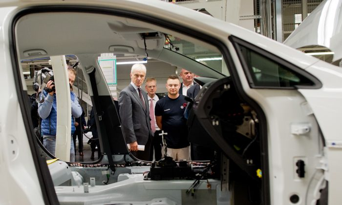 Volkswagen CEO Matthias Mueller (C) looks at the assembly line during a tour of the VW plant in Wolfsburg, Germany, on Oct. 21, 2015. (Julian Stratenschulte/AP)