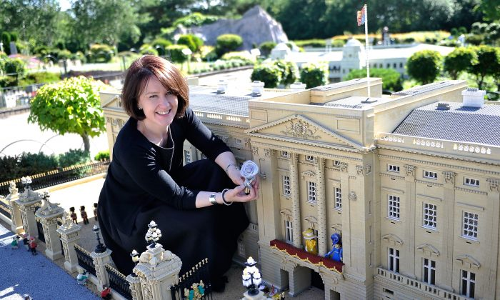 WINDSOR, ENGLAND - JUNE 10:  Rachel Trevor-Morgan, The Queen's milliner arranges LEGO figures of Camilla, Duchess of Cornwall, Queen Elizabeth II, Catherine, Duchess of Cambridge, Princess Beatrice, Princess Eugenie, Zara Tindall and Carole Middleton outside a LEGO Buckingham Palace ahead of Royal Ascot at LEGOLAND Windsor on June 10, 2014 in Windsor, England.  (Photo by Gareth Cattermole/Getty Images)
