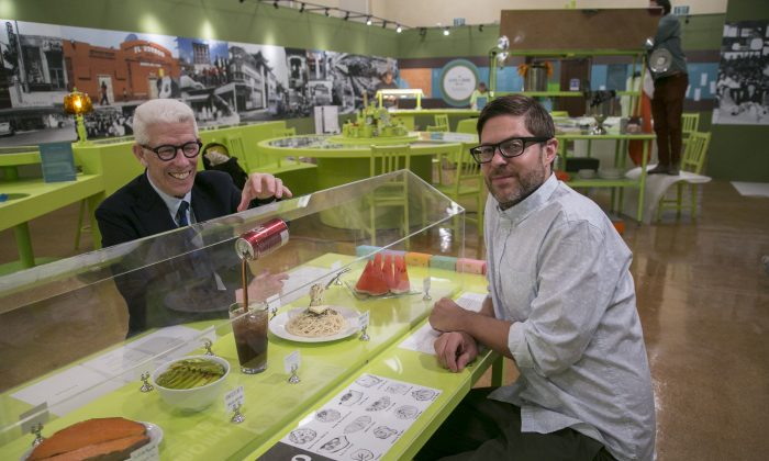 """Library Foundation of Los Angeles President Ken Brecher (L) and Josh Kun, editor and curator, sit down at the """"Invisible Kitchen"""" installation by artist Haruko Tanaka, part of the exhibit """"""""To Live and Dine in L.A."""""""" at the Los Angeles Public Library, in Los Angeles, on June 12, 2015. Two LAPL librarians began collecting menus in the 1980s. Today the library is in possession of about 15,000 menus, the oldest dating back to 1875. (AP Photo/Damian Dovarganes)"""