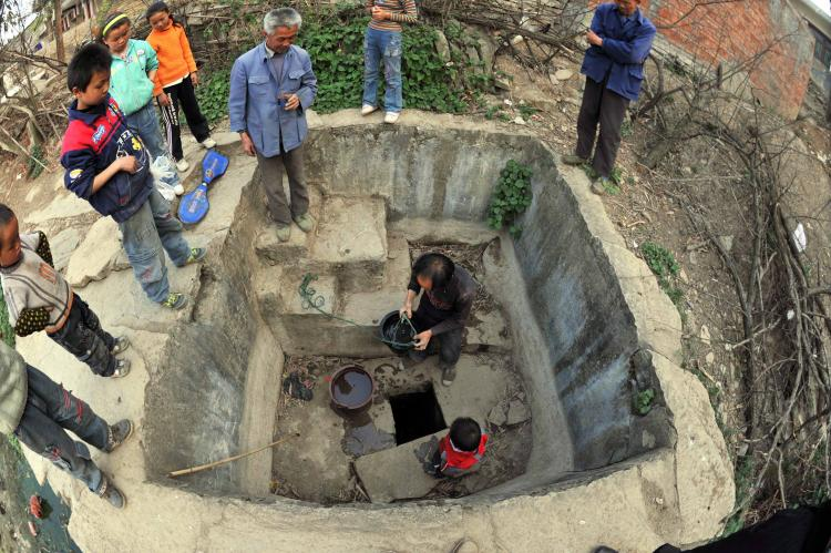 Villagers digging at a 158 year old well that no longer gives water in Guizhou Province. (Getty Images)
