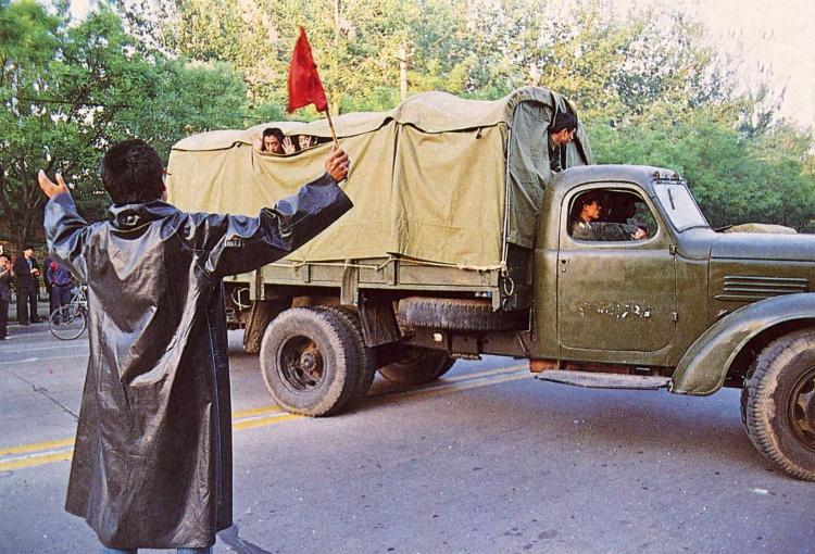 May 23rd. Soldiers wave from the back of a truck as it turns back from the city after being blocked by crowds. (64memo.com)