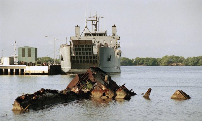 Entombed at Pearl Harbor, the remains of the USS Utah are seen in the foreground, with its eroded hulk lying in waters on the northwestern side of Ford Island, Hawaii on Nov. 22, 1991. (AP Photo/Eric Risberg)