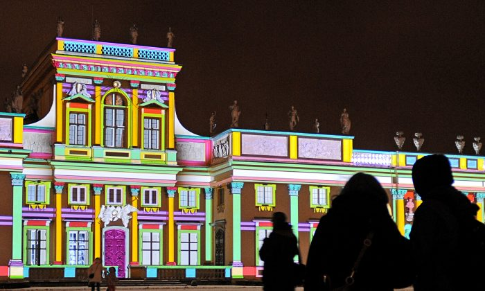 People stand in front of a specially illuminated facade of the Wilanow Royal Palace in Warsaw, Poland, on Dec. 6, 2013. The illumination is a winter attractions for tourists. (AP Photo/Alik Keplicz)