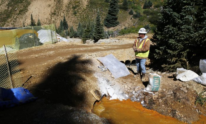 An Environmental Protection Agency contractor keeps a bag of lime on hand to correct the PH of mine wastewater flowing into a series of sediment retention ponds, part of danger mitigation in the aftermath of the blowout at the site of the Gold King Mine outside Silverton, Colo., on Aug. 14, 2015. (AP Photo/Brennan Linsley)