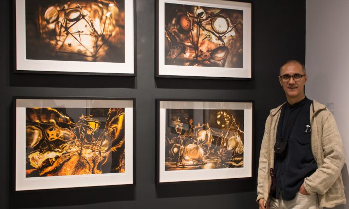 Romanian-Canadian artist Eugen-Florin Zamfirescu poses with some of his works on display at the TeodoraART Gallery in Toronto. (Elena Dumitru)